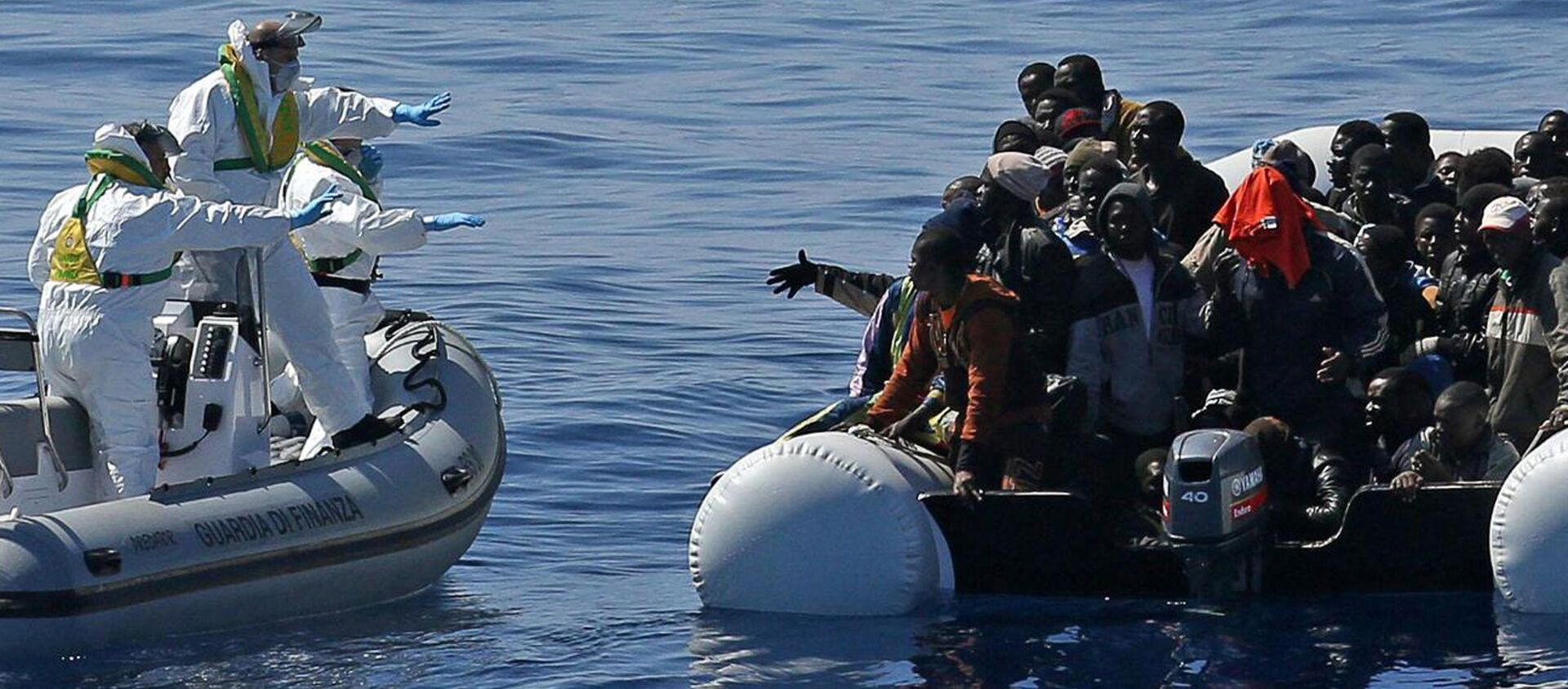 Agenti della Guardia di finanza soccorre i migranti al largo delle coste della Libia - Sputnik Italia, 1920, 02.05.2021