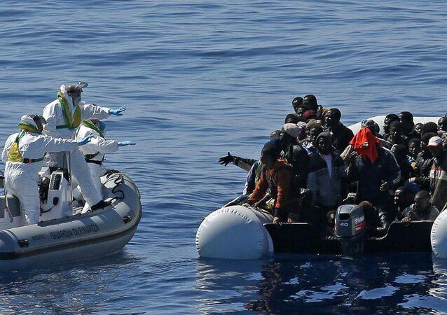 Agenti della Guardia di finanza soccorre i migranti al largo delle coste della Libia