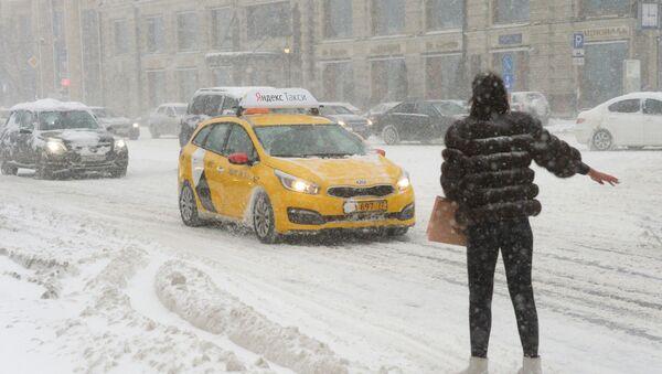 Девушка ловит такси на Тверской улице во время снегопада - Sputnik Italia