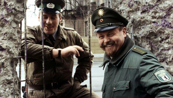 Guardia di frontiera della Germania Est e della Germania Ovest vicino al Muro di Berlino. (1990) - Sputnik Italia