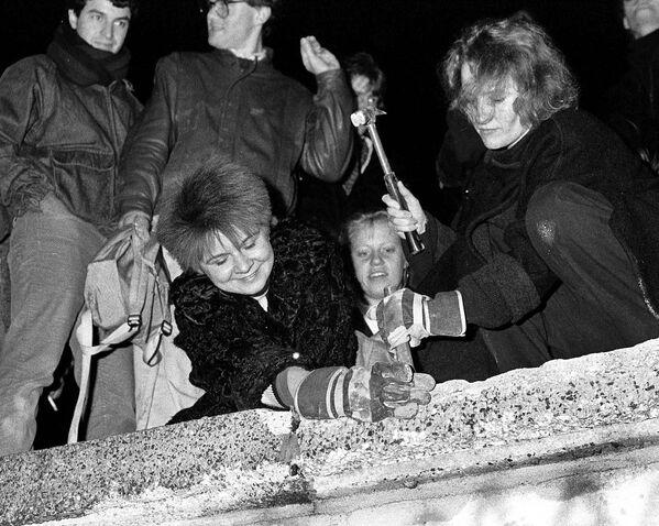 Berlinesi stanno sfacciando il Muro di Berlino. - Sputnik Italia