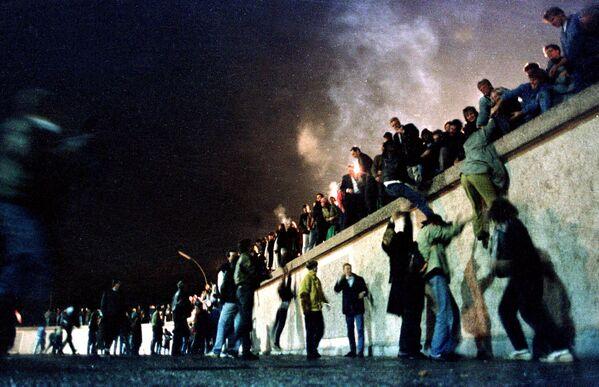 Gli abitanti di Berlino Est al Muro di Berlino dopo l'apertura delle frontiere tra le parti Est ed Ovest della città, 1989. - Sputnik Italia