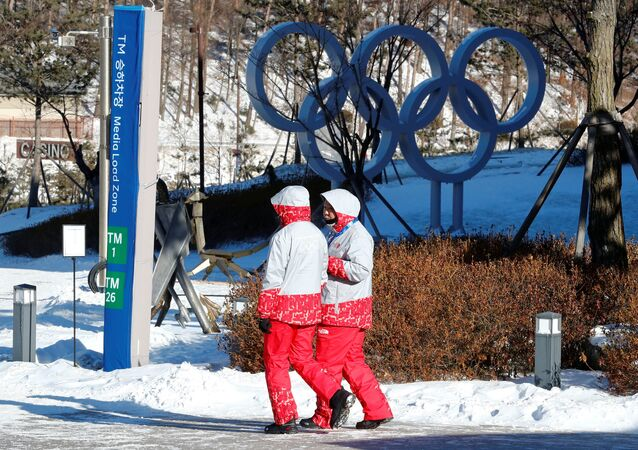 Volunteers walk beside the Olympic rings at the Alpensia resort for the upcoming 2018 Pyeongchang Winter Olympic Games in Pyeongchang, South Korea, January 23, 2018