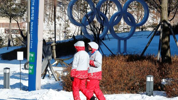 Volunteers walk beside the Olympic rings at the Alpensia resort for the upcoming 2018 Pyeongchang Winter Olympic Games in Pyeongchang, South Korea, January 23, 2018 - Sputnik Italia