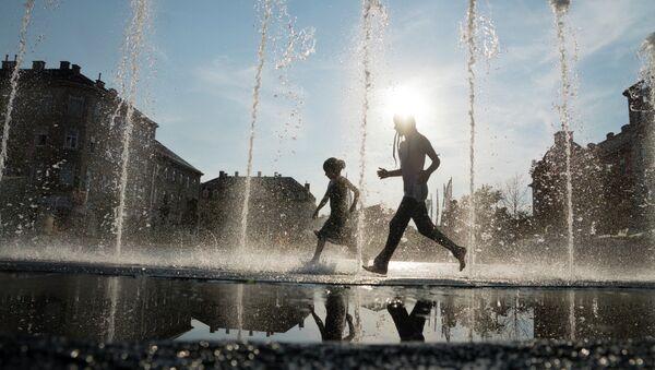 Bambini giocano in una fontana durante le ondate di calore Vienna del 2015 - Sputnik Italia
