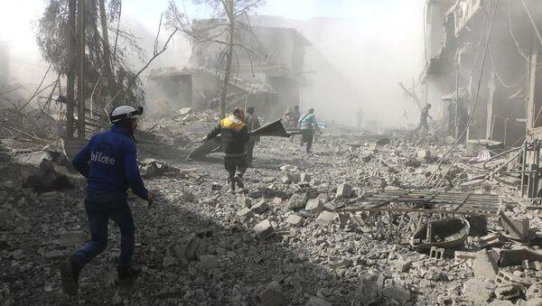 Membri della Difesa Civile siriana corrono per aiutare i sopravvissuti in una via attaccata dall'aria - Sputnik Italia
