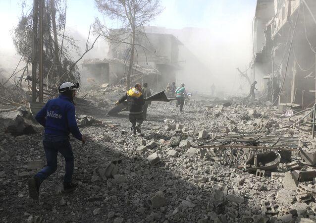 Membri della Difesa Civile siriana corrono per aiutare i sopravvissuti in una via attaccata dall'aria