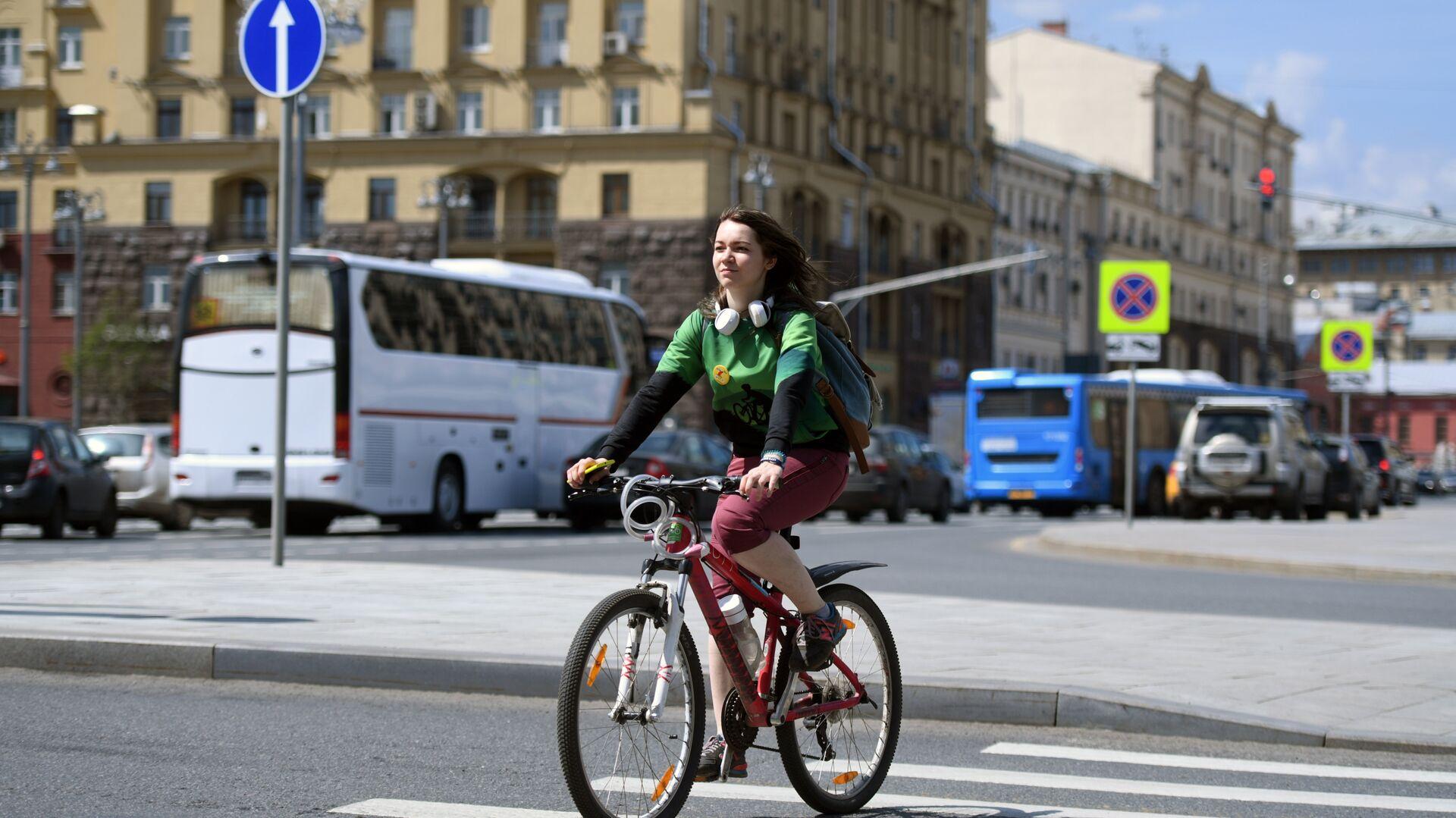Una ragazza attraversa in bicicletta una strada di Mosca - Sputnik Italia, 1920, 06.06.2021