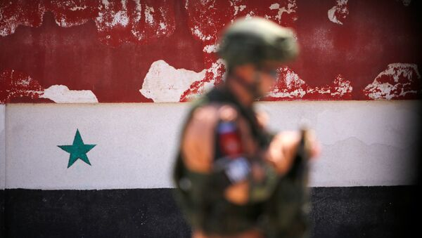A Russian soldier stands guard near a Syrian national flag drawn on the wall as rebel fighters and their families evacuate the besieged Waer district in the central Syrian city of Homs, after an agreement reached between rebels and Syria's army, Syria May 21, 2017 - Sputnik Italia