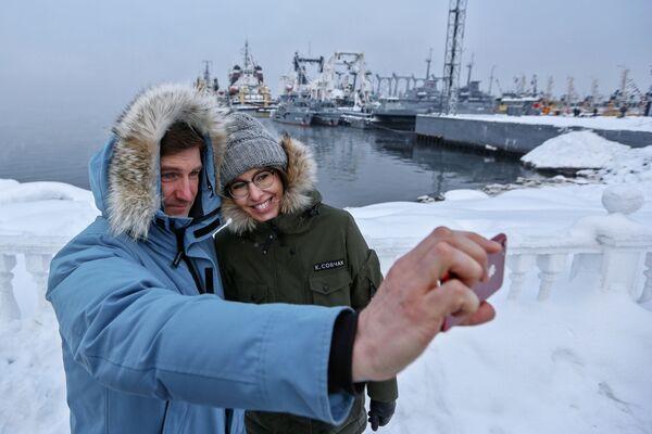 La conduttrice televisiva e la candidata alle presidenziali Ksenia Sobchak e il membro della sua squadra Anton Krasovsky sullo sfondo delle navi a Severnomorsk nella regione di Murmansk. - Sputnik Italia