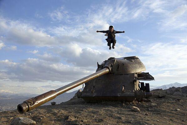Un ragazzo afghano salta da un carro armato nei pressi di Kabul. - Sputnik Italia