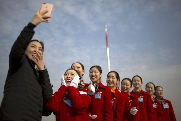 Ragazze-hostess si fanno un selfie durante le seduta della riunione pancinese dei rappresentanti popolari a Pechino. - Sputnik Italia