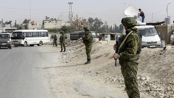 Russian military police members stand guard at the Wafideen checkpoint on the outskirts of the Syrian capital Damascus neighbouring the rebel-held Eastern Ghouta enclave on March 13, 2018, awaiting any civilians evacuating from the area - Sputnik Italia