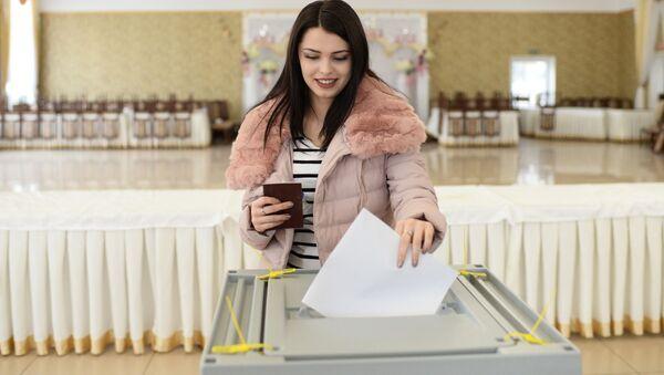 Девушка опускает бюллетень в урну на выборах президента РФ на избирательном участке в Бахчисарае - Sputnik Italia