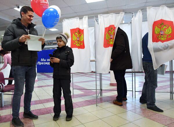 Un papà al seggio elettorale con suo figlio domenica 18 marzo 2018 - Sputnik Italia