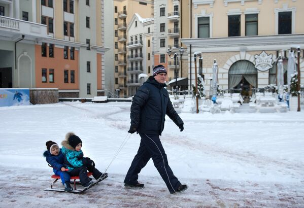 Un papà trasporta i suoi due figli su una slitta per le vie del paese di Roza Khutor, sulle montagne olimpiche di Sochi - Sputnik Italia