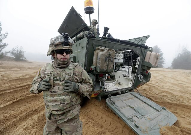 Soldato americano sullo sfondo del blindato Stryker