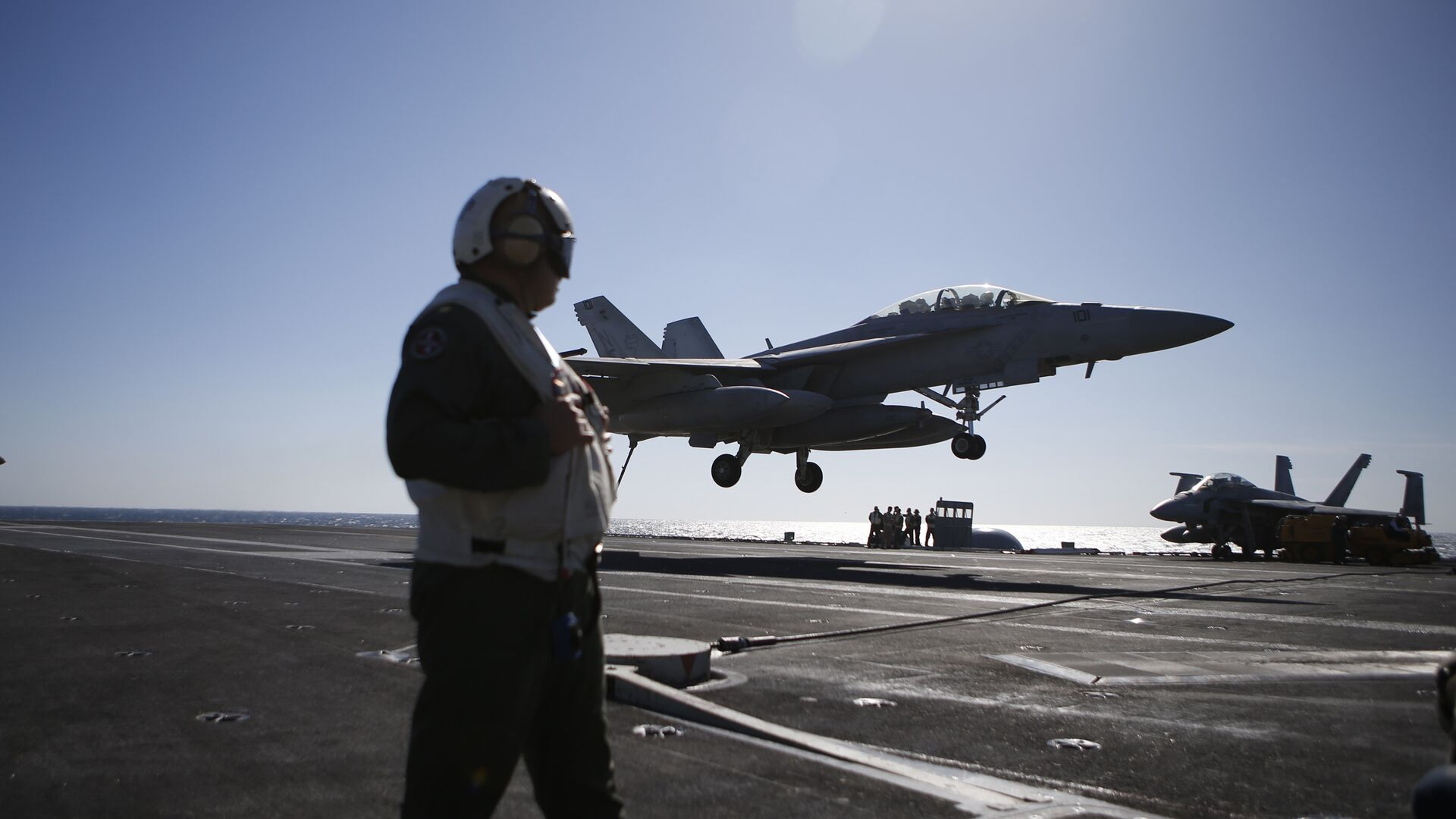 A US Navy crew member looks at an F/A-18 Super Hornet fighter landing onto the deck of the USS Ronald Reagan, a Nimitz-class nuclear-powered aircraft carrier, during a joint naval drill between South Korea and the US in the West Sea off South Korea on October 28, 2015 - Sputnik Italia, 1920, 07.06.2021
