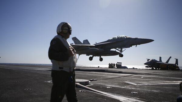 Un marines osserva l'atterraggio di un F/A-18 Super Hornet da una portaerei americana - Sputnik Italia
