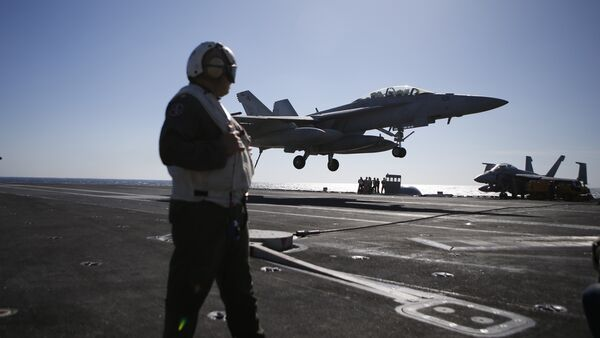 A US Navy crew member looks at an F/A-18 Super Hornet fighter landing onto the deck of the USS Ronald Reagan, a Nimitz-class nuclear-powered aircraft carrier, during a joint naval drill between South Korea and the US in the West Sea off South Korea on October 28, 2015 - Sputnik Italia