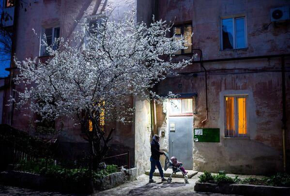 Una donna con sua figlia viste all'uscita di una casa residenziale a Sebastopoli, Crimea, Russia. - Sputnik Italia