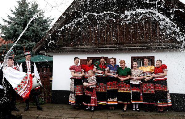 Uomini annaffiano le donne con l'acqua durante le celebrazioni di Pasqua a Mezokovesd, Ungheria. - Sputnik Italia