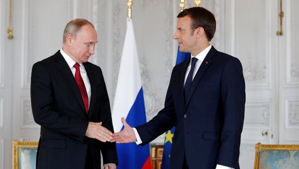 French President Emmanuel Macron shakes hands Russian President Vladimir Putin (L) at the Chateau de Versailles as they meet for talks before the opening of an exhibition marking 300 years of diplomatic ties between the two countyies in Versailles, France, May 29, 2017 - Sputnik Italia