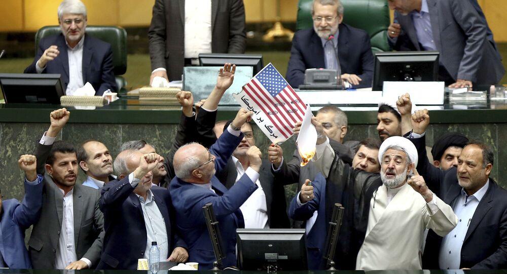 Le immagini della bandiera statunitense e dell'accordo nucleare vengono bruciate nel parlamento dell'Iran