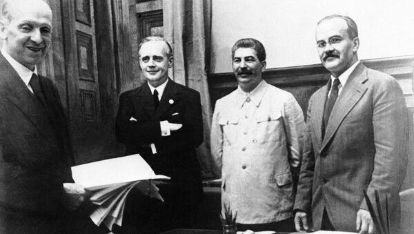 Firma del trattato da parte di Molotov alla presenza di Ribbentrop e Stalin, il 23 agosto 1939. - Sputnik Italia