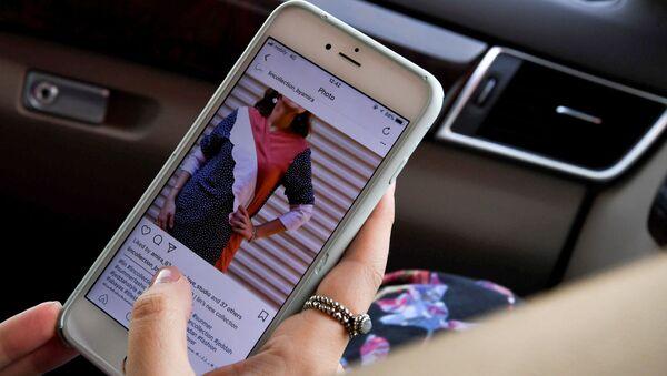 Una ragazza aggiorna Instagram sul proprio smartphone - Sputnik Italia