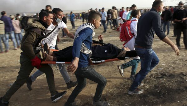 Palestinian protesters evacuate a wounded woman during clashes with Israeli troops along Gaza's border with Israel, Friday, April 13, 2018. - Sputnik Italia