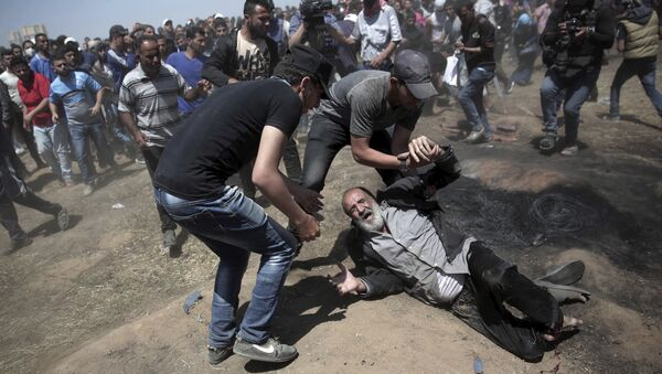 An elderly Palestinian man falls on the ground after being shot by Israeli troops during a deadly protest at the Gaza Strip's border with Israel, east of Khan Younis, Gaza Strip, Monday, May 14, 2018 - Sputnik Italia