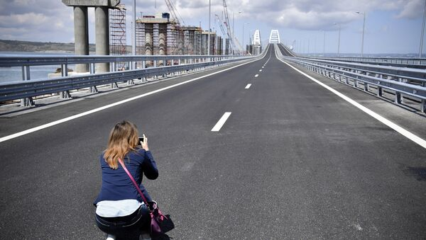 A journalist takes a photograph of the new bridge linking Russia and the Crimean peninsula prior to the opening ceremony near Kerch, Crimea, Tuesday, May 15, 2018 - Sputnik Italia