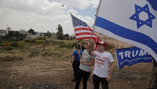 Gli israeliani tengono le bandiere degli USA e dell'Israele di fronte alla nuova ambasciata USA a Gerusalemme. - Sputnik Italia