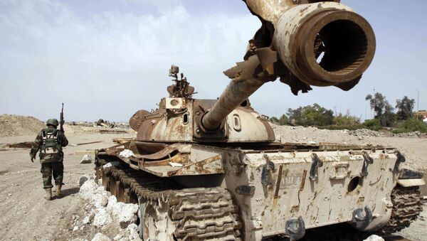 An Iraqi soldier is seen near an Iraqi Army tank, which was destroyed in the US-led invasion, in Basra, Iraq's second-largest city, 550 kilometers (340 miles) southeast of Baghdad, Iraq, Thursday, April 9, 2009 - Sputnik Italia