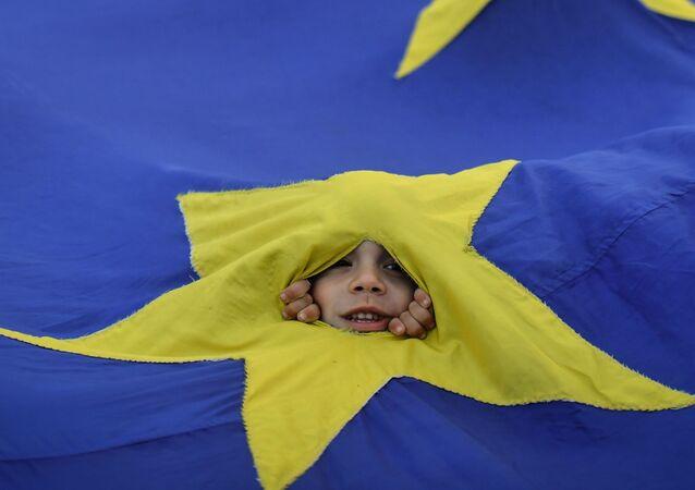 Un bambino guarda tra la bandiera dell'UE durante una manifestazione a Bucarest.
