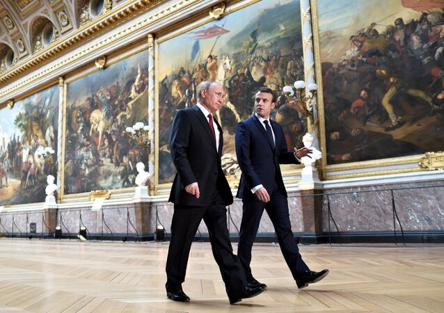 French President Emmanuel Macron (R) speaks to Russian President Vladimir Putin (L) in the Galerie des Batailles (Gallery of Battles) as they arrive for a joint press conference at the Chateau de Versailles before the opening of an exhibition marking 300 years of diplomatic ties between the two countries in Versailles, France, May 29, 2017