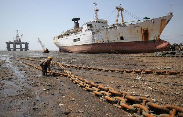 I lavoratori stringono la corda legata alla torre di estrazione del petrolio fuori uso in India. - Sputnik Italia