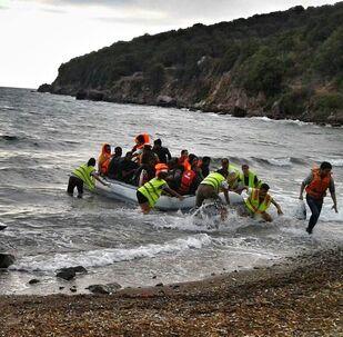 Un gommone di migranti approda su una spiaggia del Mediterraneo