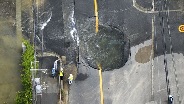 L'aqcua va dalle crepe in una strada distrutta dal terremoto a Takatsuki, Osaka, Giappone occidentale - Sputnik Italia