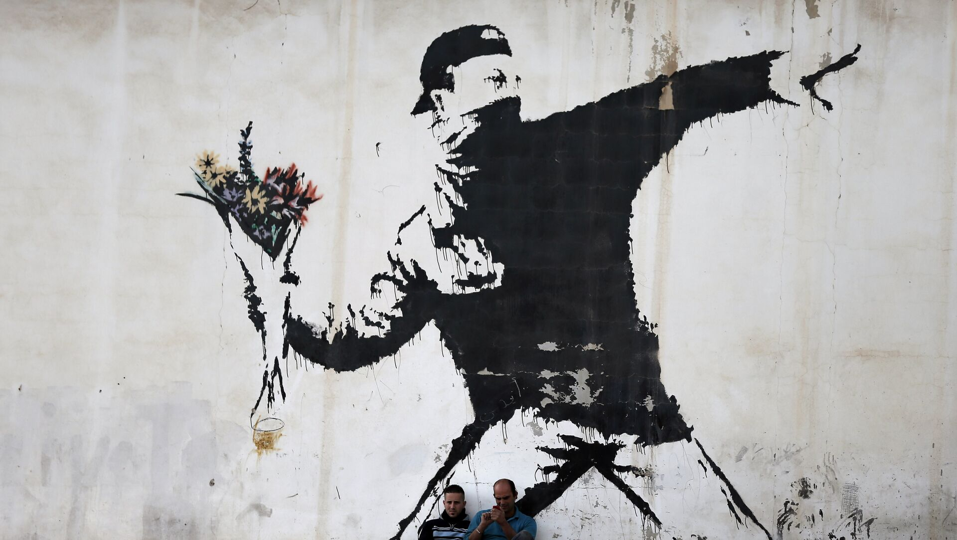 Two men are sitting in front of a famous graffiti of British street artist Banksy, painted on a wall of a gas station in the West Bank city of Bethlehem on December 16, 2015.  - Sputnik Italia, 1920, 13.05.2021