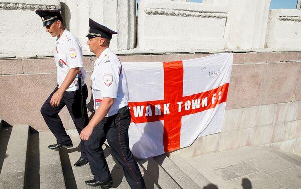 Poliziotti russi camminano davanti ad una bandiera inglese appesa dai tifosi a Volgograd - Sputnik Italia