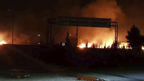 In questa foto del 9 maggio 2018 si vedono le fiamme alzarsi nel cielo dopo un attacco contro le basi siriane di Kiwse, sobborgo a sud di Damasco - Sputnik Italia