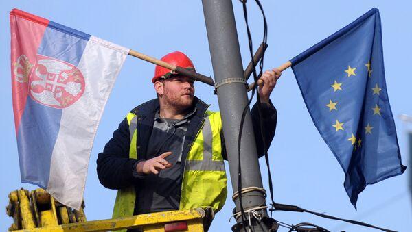A worker arranges flags of Serbia and EU on a lamppost in Belgrade (File) - Sputnik Italia
