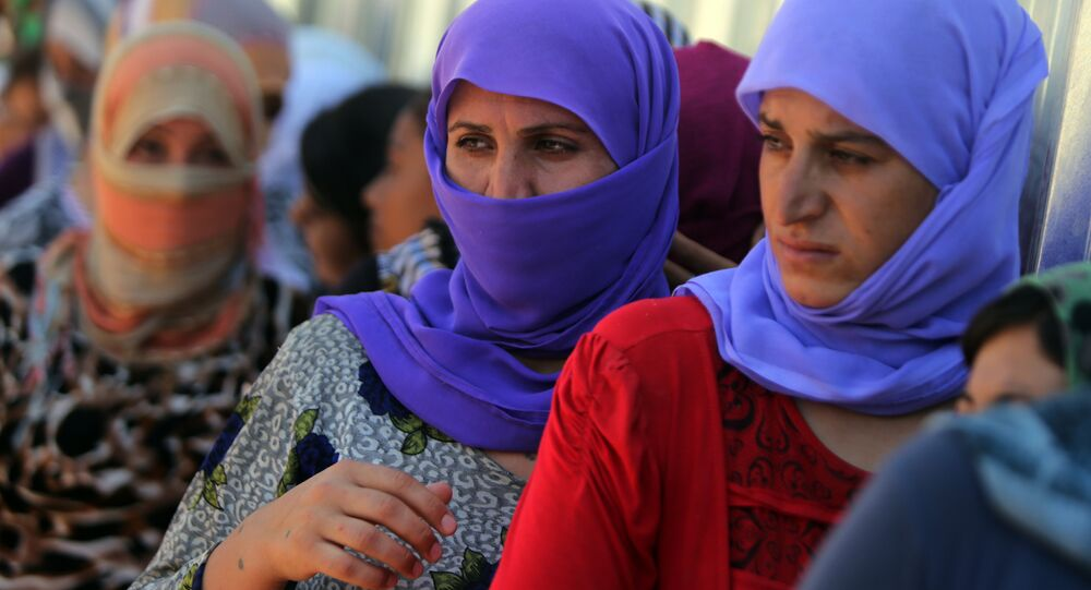Yazidi Iraqi women queue in order to get food at the Bajid Kandala camp near the Tigris River, in Kurdistan's western Dohuk province, where they took refuge after fleeing advances by Islamic State jihadists in Iraq on August 13, 2014. (File)