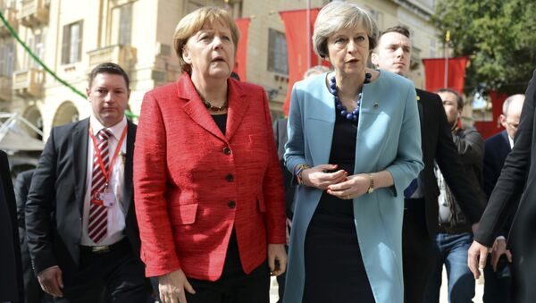 German Chancellor Angela Merkel, left, speaks with British Prime Minister Theresa May, right, as they walk with other EU leaders during an event at an EU summit in Valletta, Malta, on Friday, Feb. 3, 2017. - Sputnik Italia