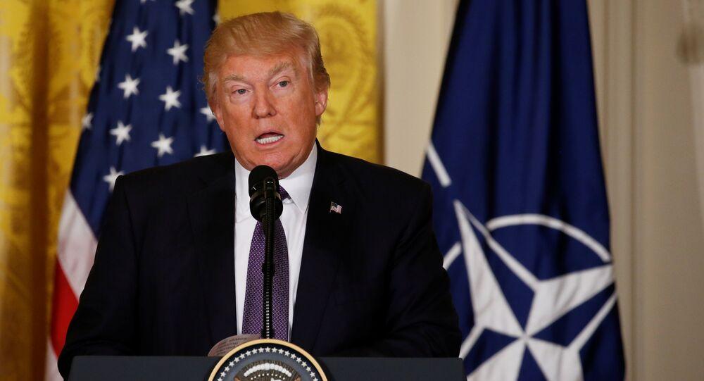 Donald Trump sullo sfondo di bandiere USA e NATO