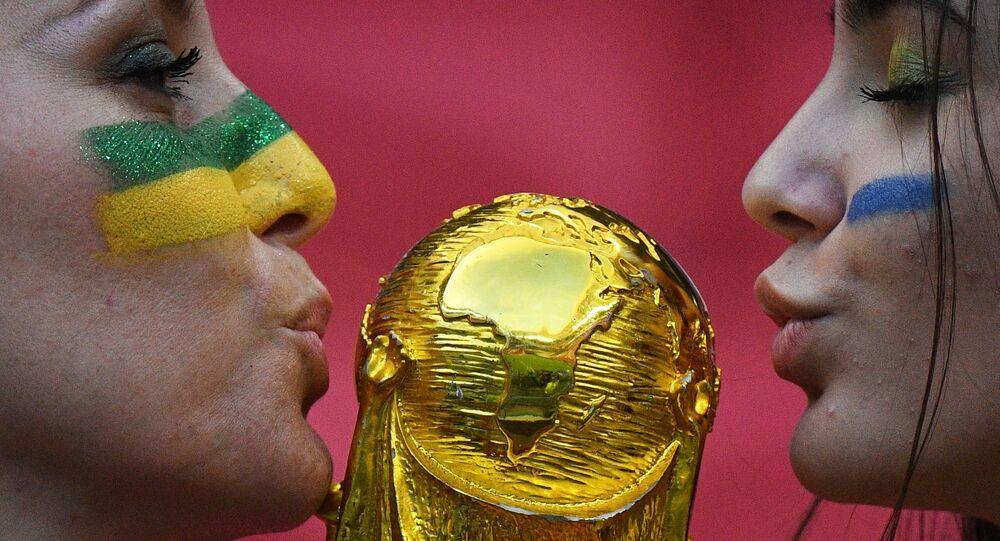 Due ragazze baciano la coppa del Mondo