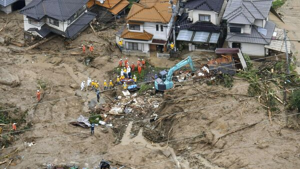 Rescue workers are seen next to houses damaged by a landslide following heavy rain in Hiroshima, western Japan, in this photo taken by Kyodo July 7, 2018 - Sputnik Italia