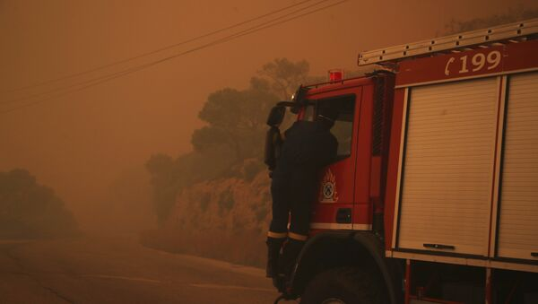 A fire truck is engulfed in a pall of orange smoke on a road near Kineta, west of Athens, Monday, July 23, 2018. - Sputnik Italia